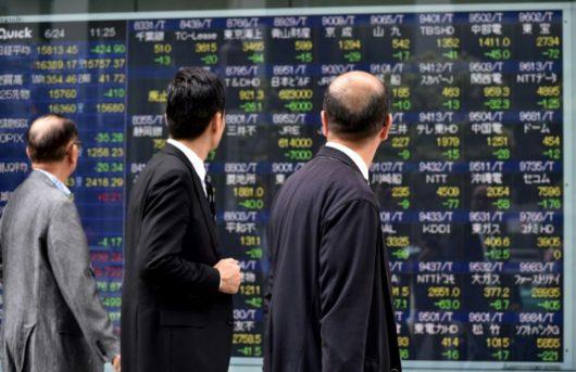 887783-des-passants-regardent-un-ecran-montrant-des-donnees-boursieres-a-tokyo-capitale-du-japon-le-24-juin